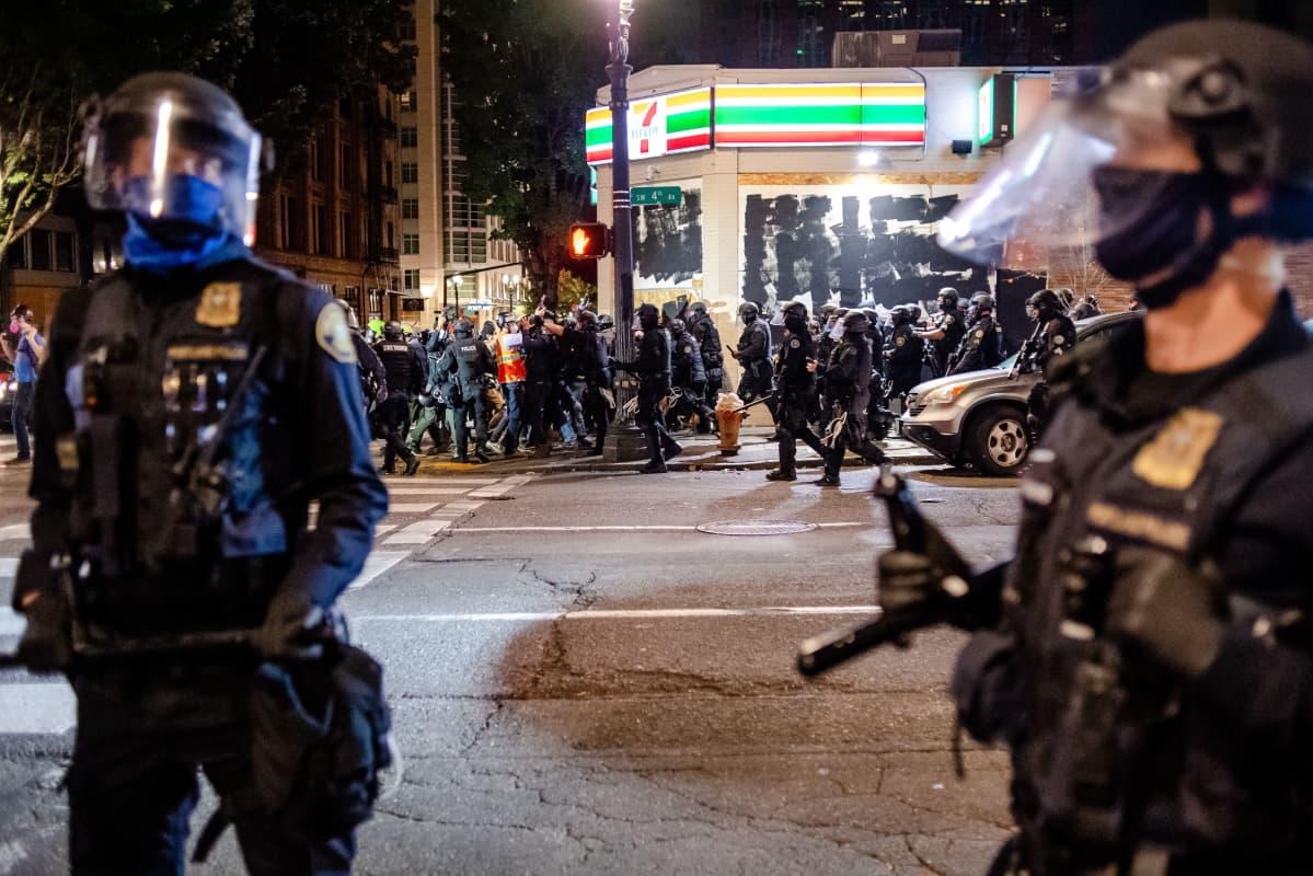 Iltavalaistuksessa kaupunkikuvassa näkyy mellakavarusteisia poliiseja ja taustalla mielenosoittajia.