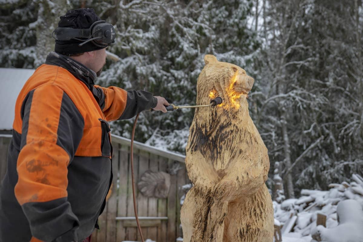 Raimo Hautaluoma pintakäsittelee puukarhua