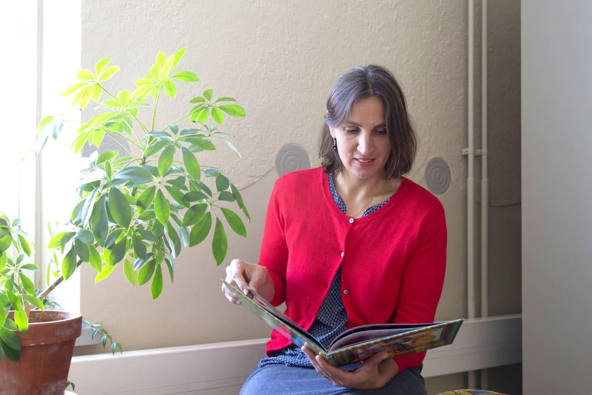 Lastenkirjaininstituutin toiminnanjohtaja Kaisa Laaksonen istuu ikkunalaudalla ja selaa lastenkirjaa.