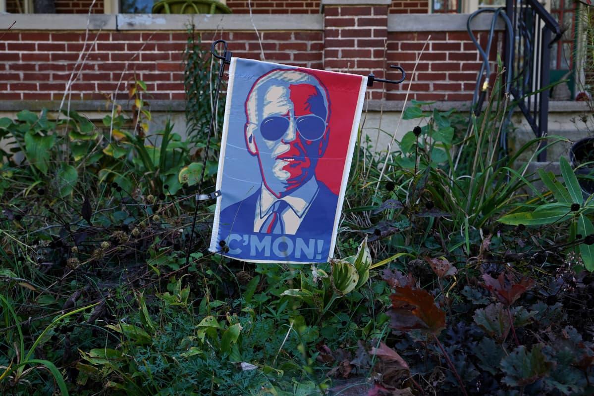 Joe Bidenia kannatta kyltti puutarhassa. Punavalkosinisessä kyltissä on Bidenin kuva ja teksti C'mon!.