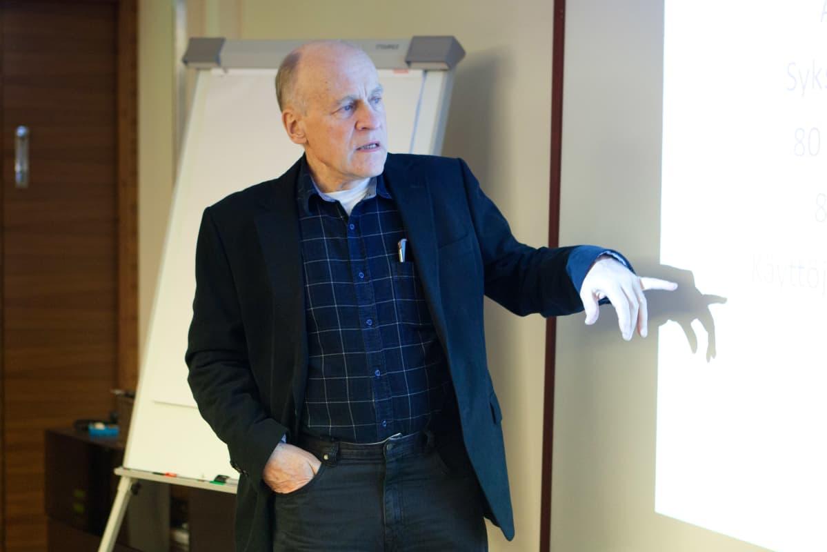 Yrittäjä Matti Häll seisoo kuvassa fläppitaulun edessä.