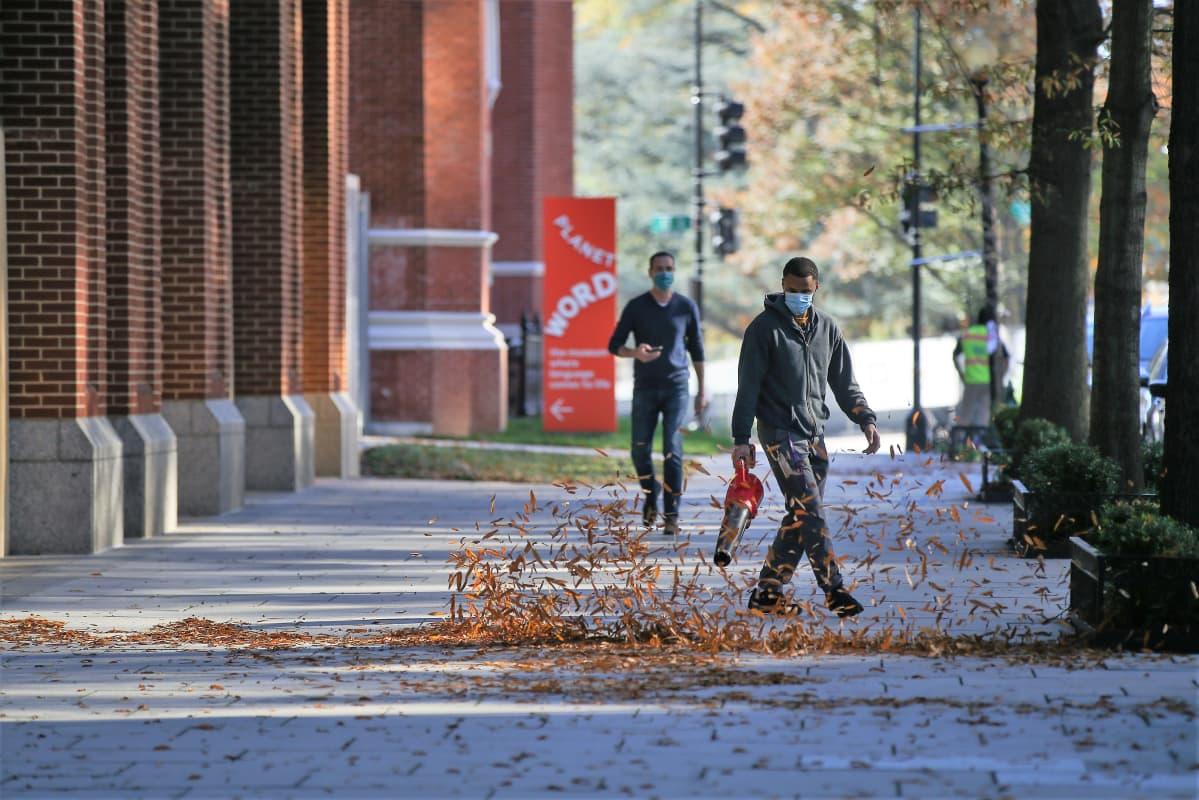 Mies puhaltaa lehtipuhaltimella lehtiä kadulta. Taustalla näkyy kävelijä. Molemmilla on maskit kasvoillaan.