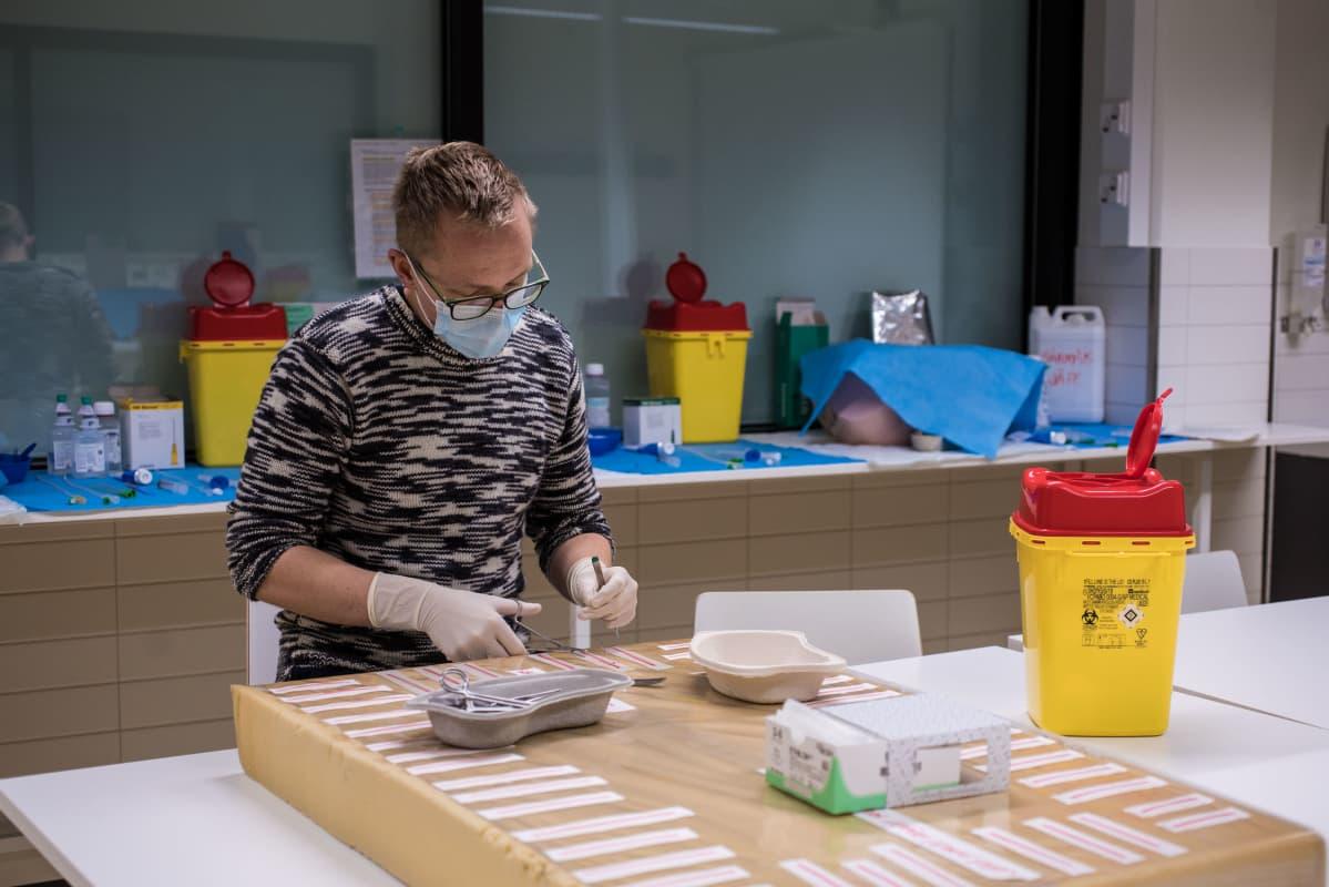 Lääketieteen kandi Riku Metsälä harjoittelee suturointia eli haavan kiinni ompelemista Tampereen yliopiston Kaupin kampuksella.