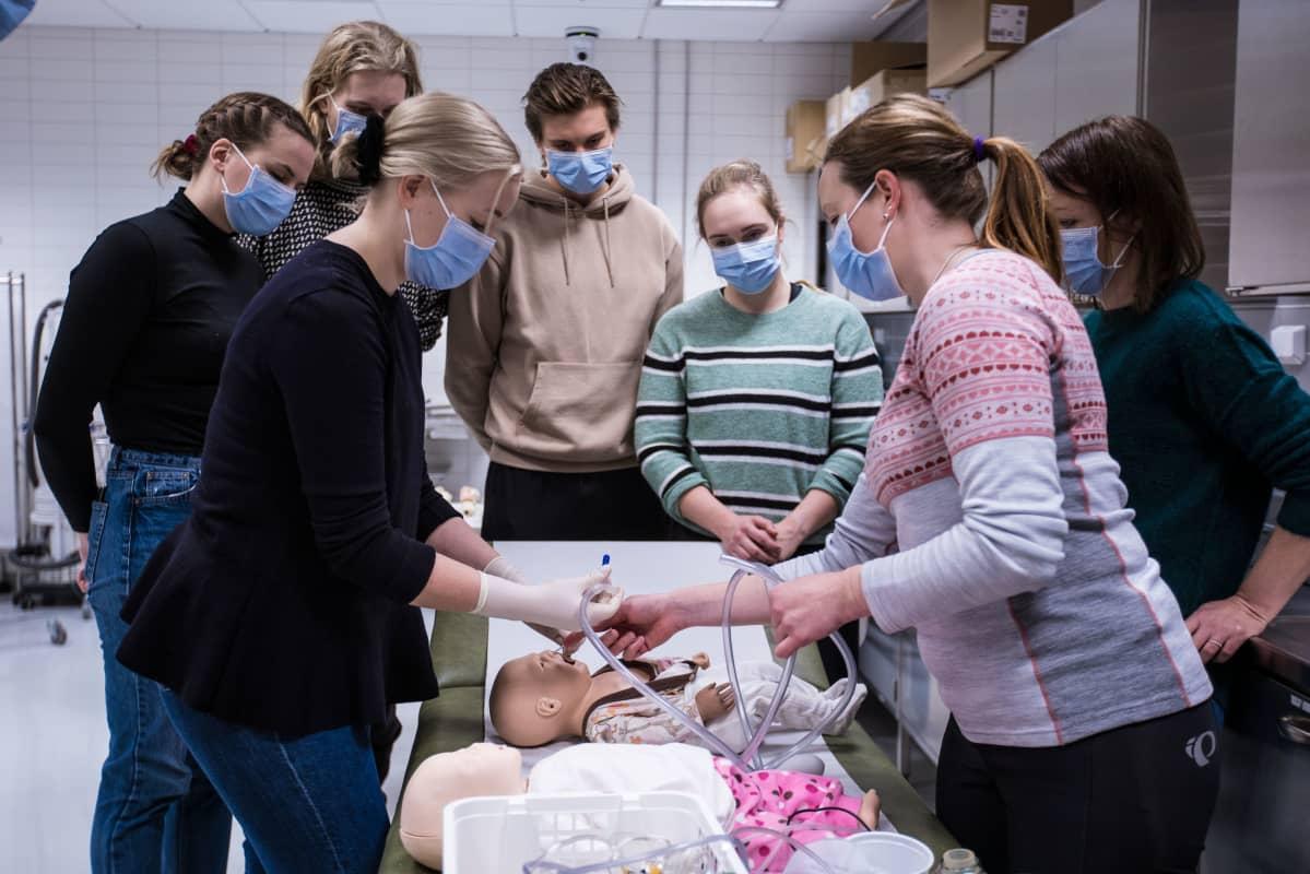 Sairaanhoitaja ja opetuskoordinaattori Hanna Väärälä (poninhäntä) ja opettaja Sari Törmänen opastavat viidennen vuosikurssin lääkäriopiskelijoille huonokuntoisen vauvan hengityksen tarkistamista. Etualalla opiskelija Aino Pitkänen (vaalea tukka).