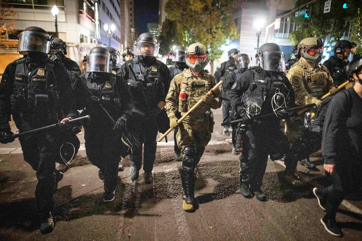 Rivi mellakkapoliiseja ja kansalliskaartin jäseniä kulkee iltaisella kadulla raskaassa varustuksessa.