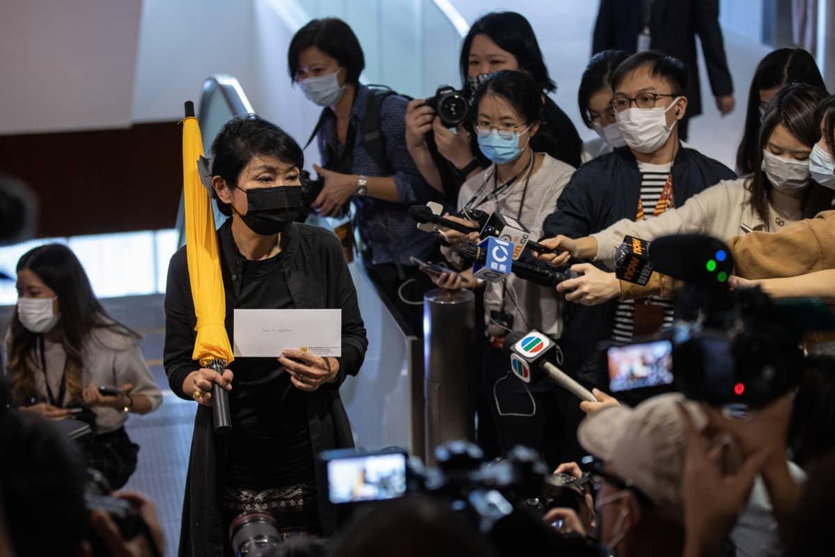 Claudia Mo Man-ching toi irtisanoutumiskirjeensä lainsäädäntöneuvostoon 12. marraskuuta 2020. Ei ole tiedossa, onko hänen kantamansa sateenvarjolla symbolista merkitystä: keltainen sateenvarjo on demokratiamielenosoitusten symboli vuosien takaa.