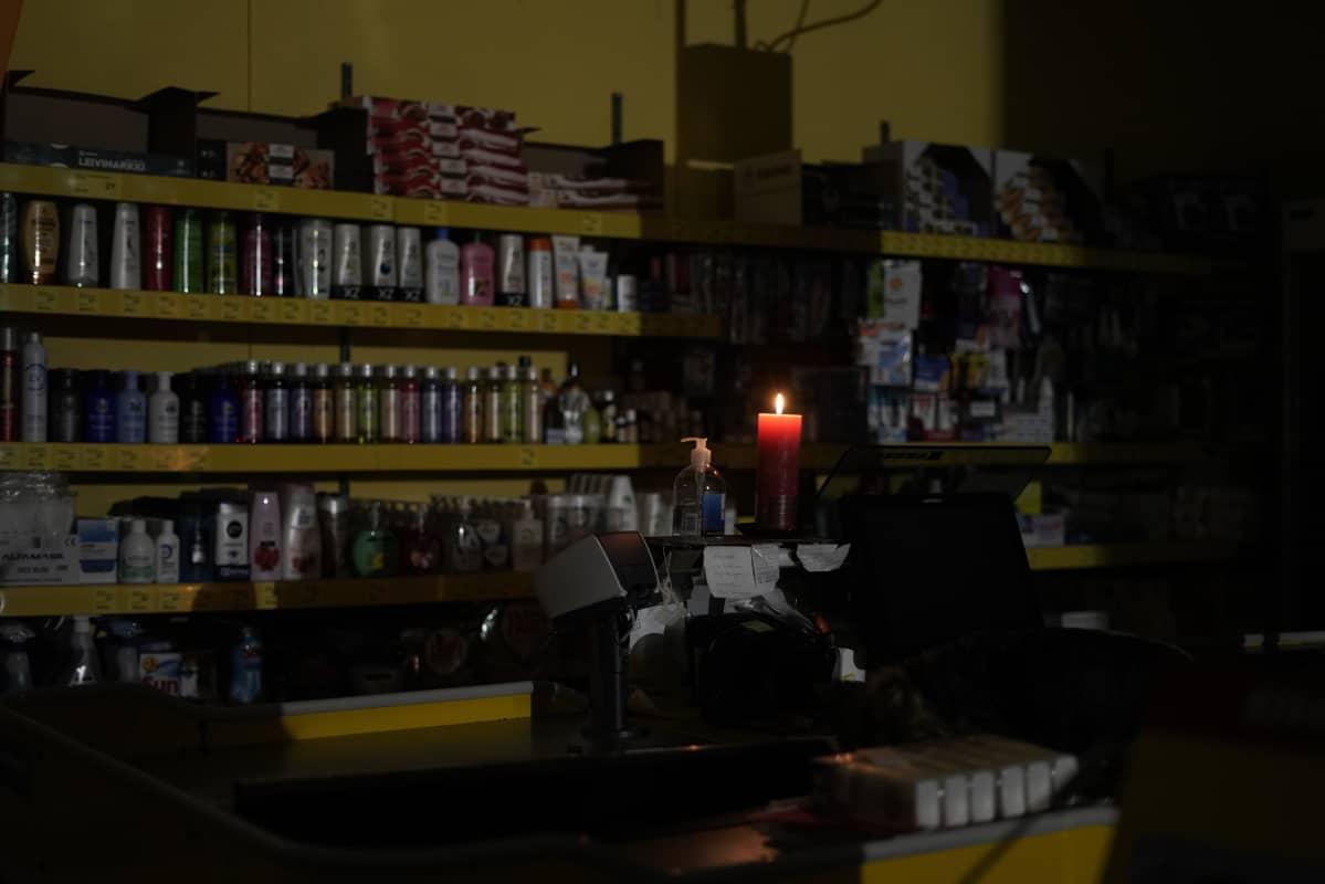 Kynttilä palaa pimeässä kyläkaupassa.