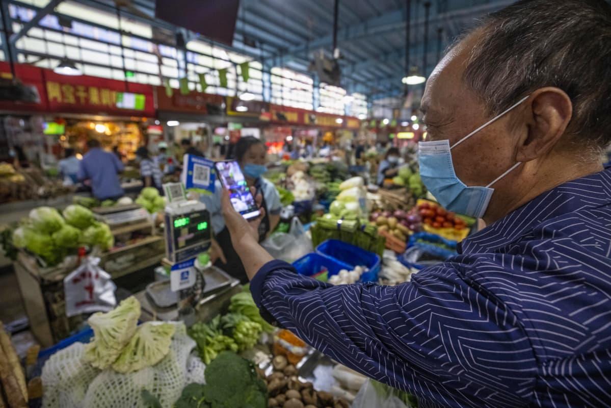 Kiinan Hangzhoussa tuoretuotteita myyvällä torilla asiakas skannasi QR-maksukoodia ostosten tekemistä varten 27. syyskuuta 2020.