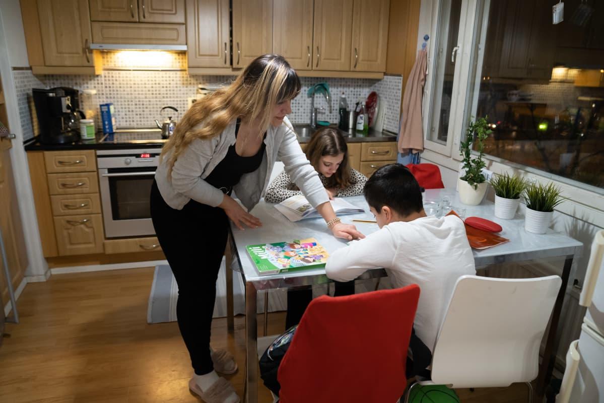 Mirna Alsaddir auttaa lapsiaan läksyjen teossa.