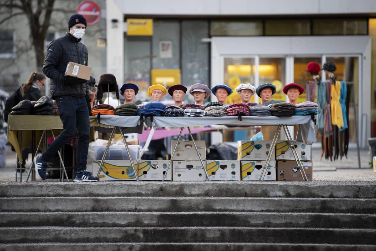 Maskiin pukeutunut kävelee hattukauppiaan myyntipöydän edustalla ostoskeskuksen pihalla.