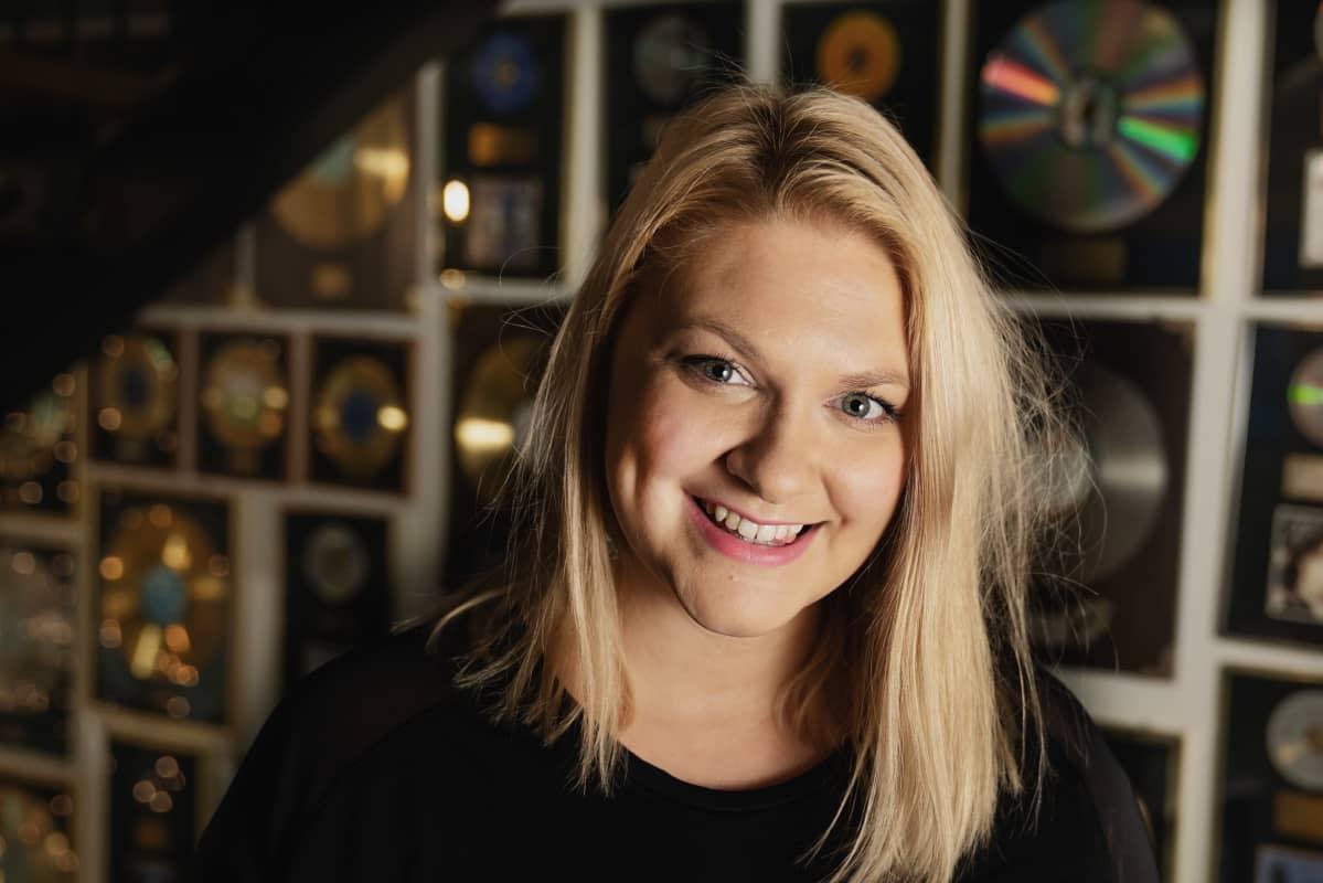 Karoliina Kanerva hymyilee lähikuvassa Warner Music Finlandin tiloissa, taustalla seinä täynnä kultalev.