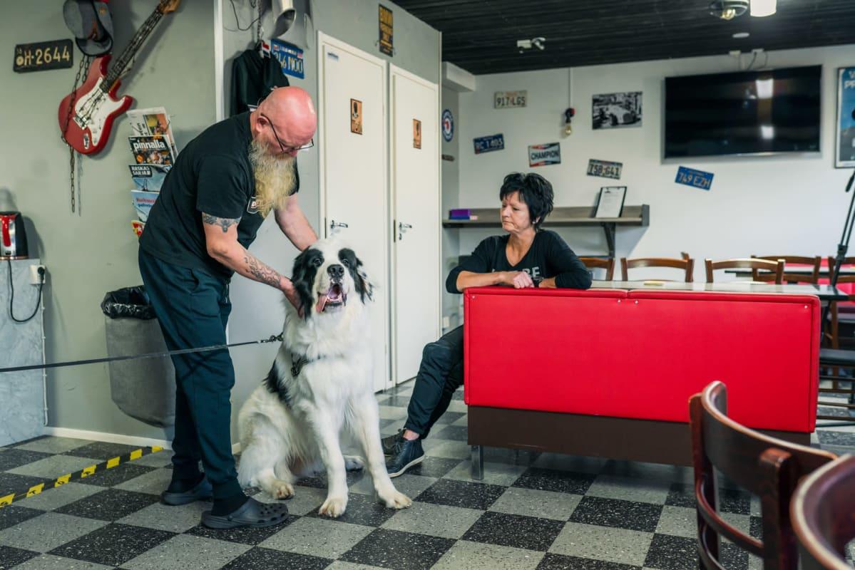 Tapio ja Eila Leppänen tervehtivän baarissaan vierailevaa Rolli-koiraa.