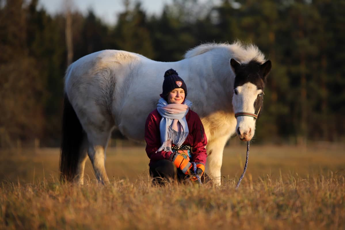 Mila Tanttu on kyykyssä islanninhevosen vieressä pellolla.