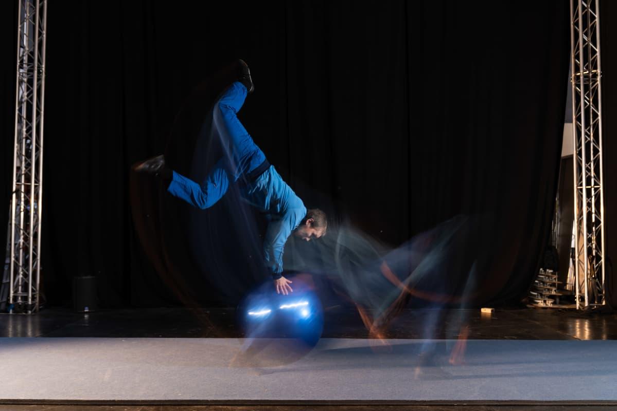 Rauli Dahlberg tekee akrobatiatemppuja fitnesspallon kanssa.