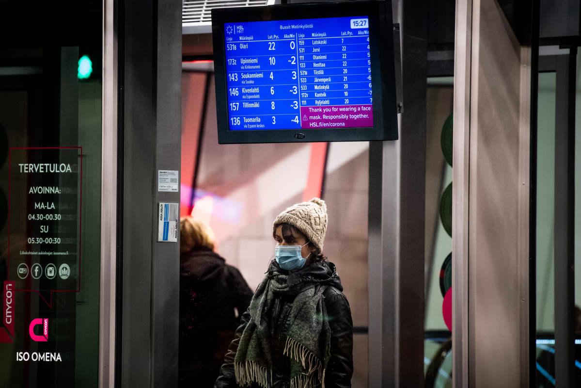 Nainen odottaa bussia aikataulunäytön alla kasvomaskilla suojautuneena.