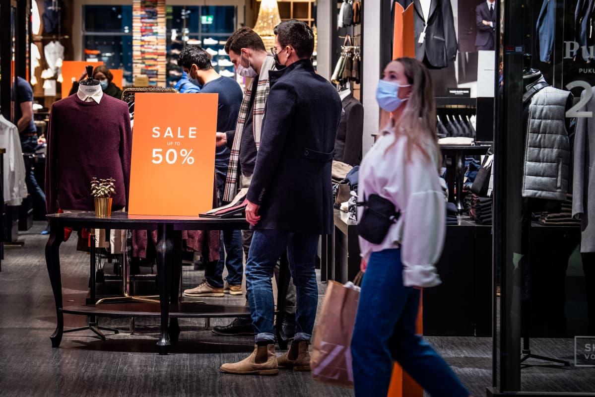 Miehet katselevat vaatekaupassa alennuksessa olevia tuotteita.