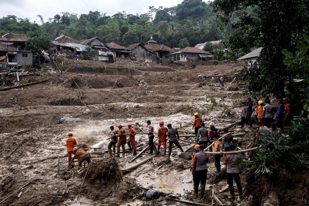 Pelastustyöntekijät siivoavat maanvyörymän jälkiä ja etsivät kadonneita ihmisiä Indonesiassa.