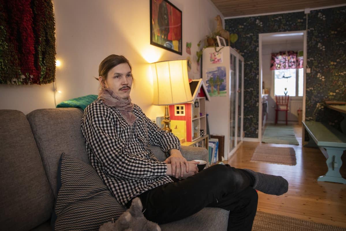 Joonatan Tola istuu sohvalla olohuoneessaan