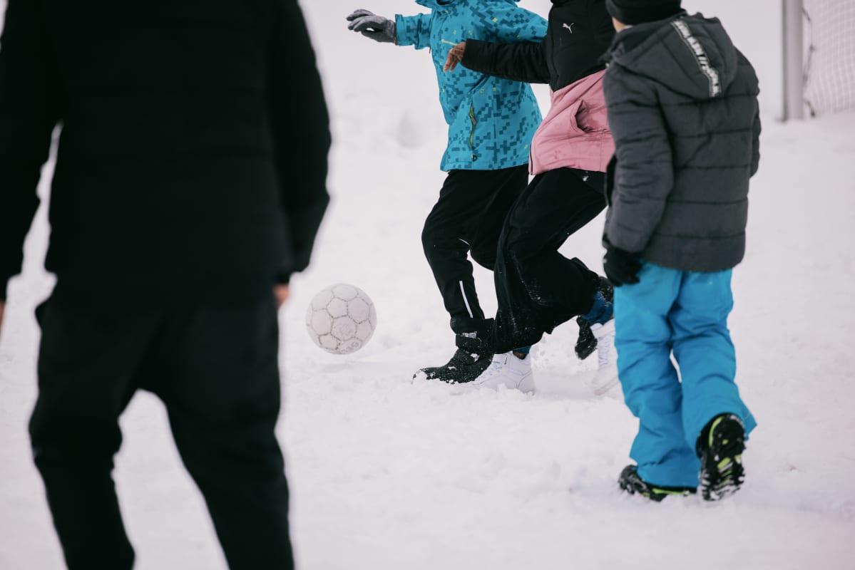 Oppilaat pelaavat jalkapalloa välitunnilla.