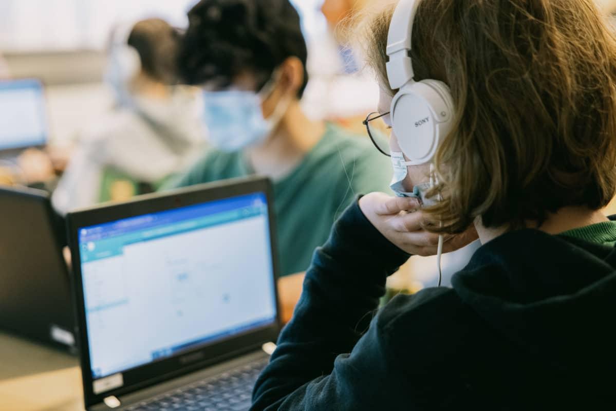 Oppilaat käyttävät tietokoneita kasvomaskit päällä.