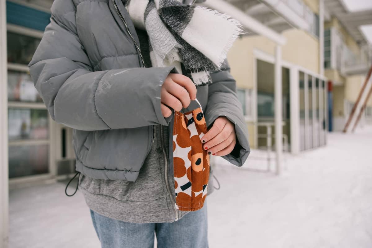 Oppilas kasvomaski kädessä välitunnilla.