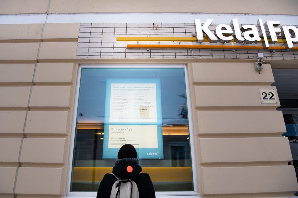 Henkilö seisoo Kelan ikkunassa olevan eri palvelunumeroista kertovan ohjeen edessä.