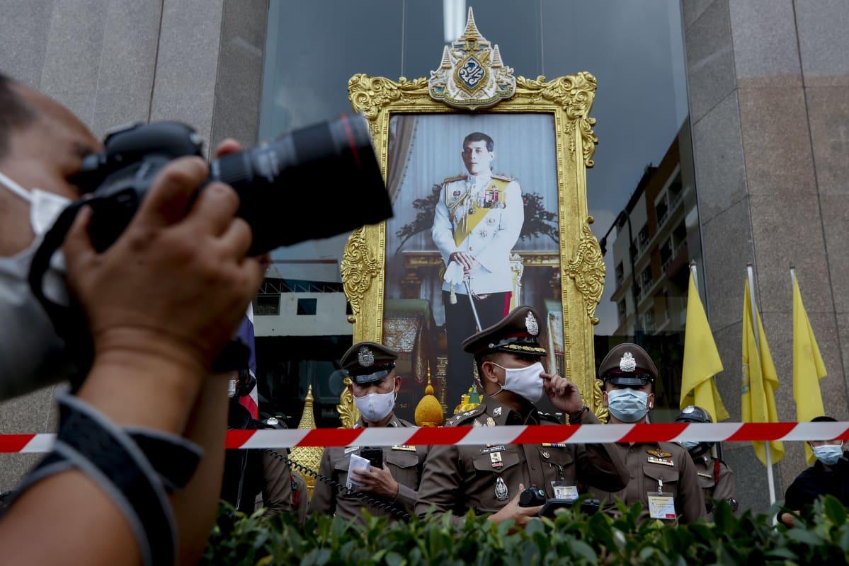 Poliisi valvoi kuninkaan kuvan edessä demokratiamielenosoitusta Bangkokissa tammikuussa.