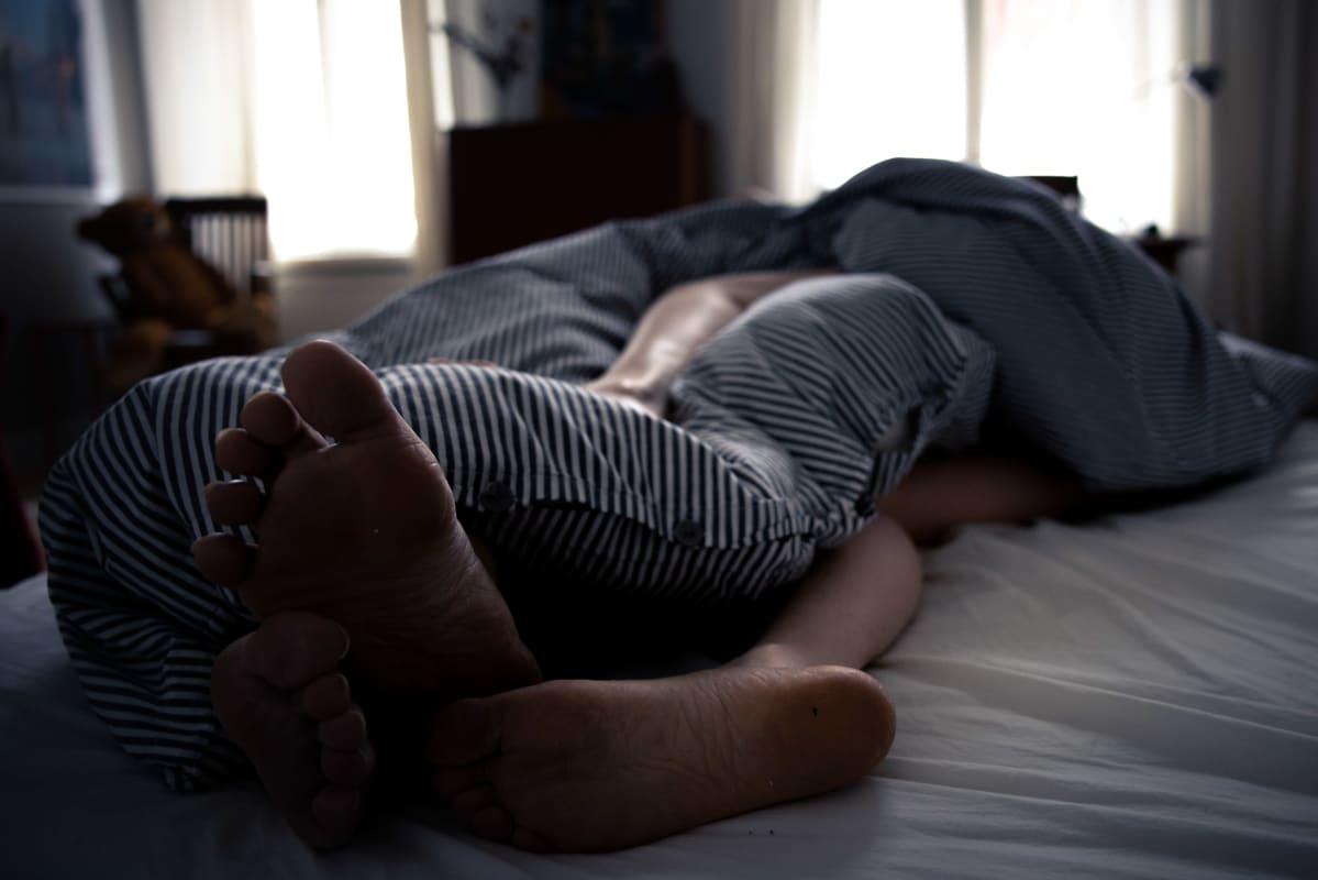 Kaksi henkilöä sängyssä peiton alla.