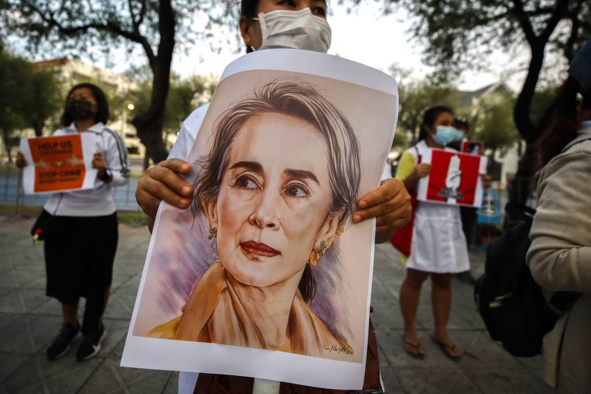 Mielenosoittajalla on kyltti, jossa on Aung San Suu Kyin kuva