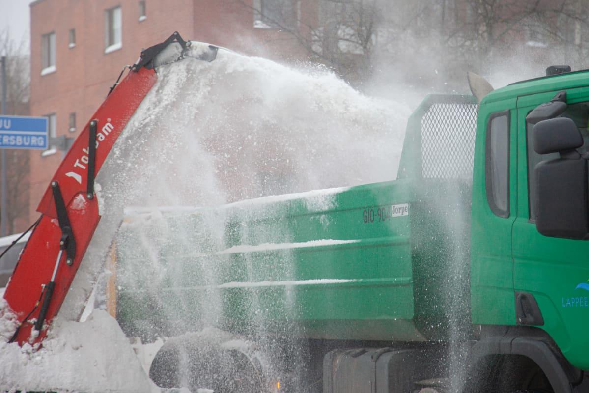 Traktoriin kiinnitetty lumilinko linkoaa lunta kadunvarresta kuorma-auton kyytiin Lappeenrannan keskustassa.