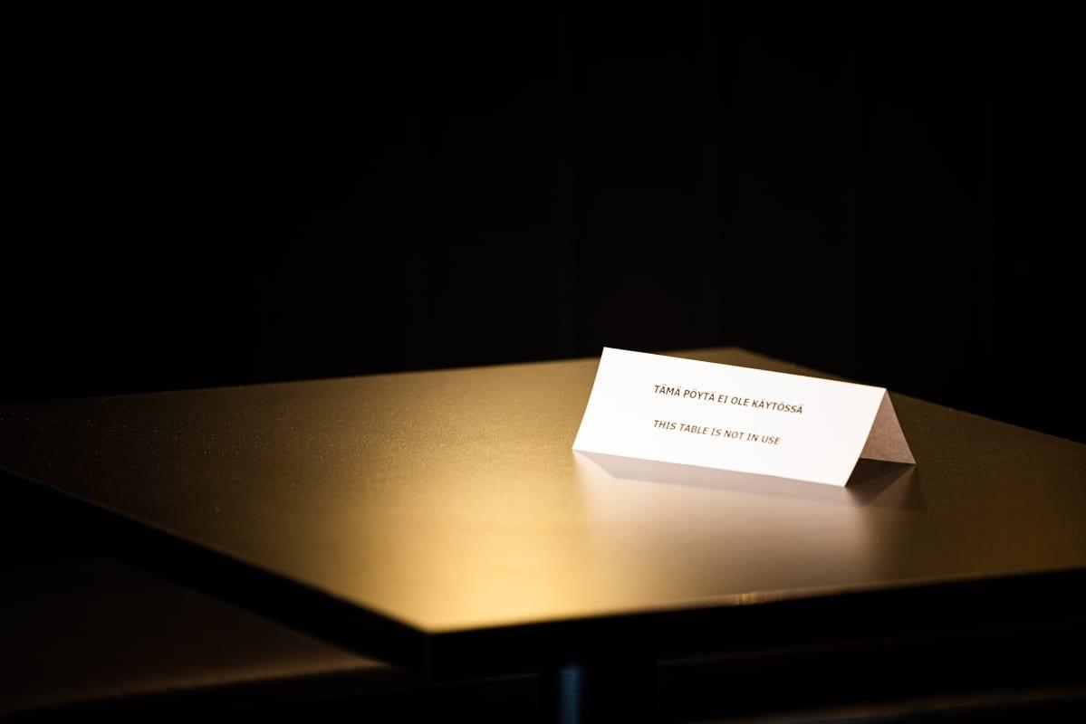 Ravintola pöydällä lappu jossa lukee tämä pöytä ei ole käytössä.