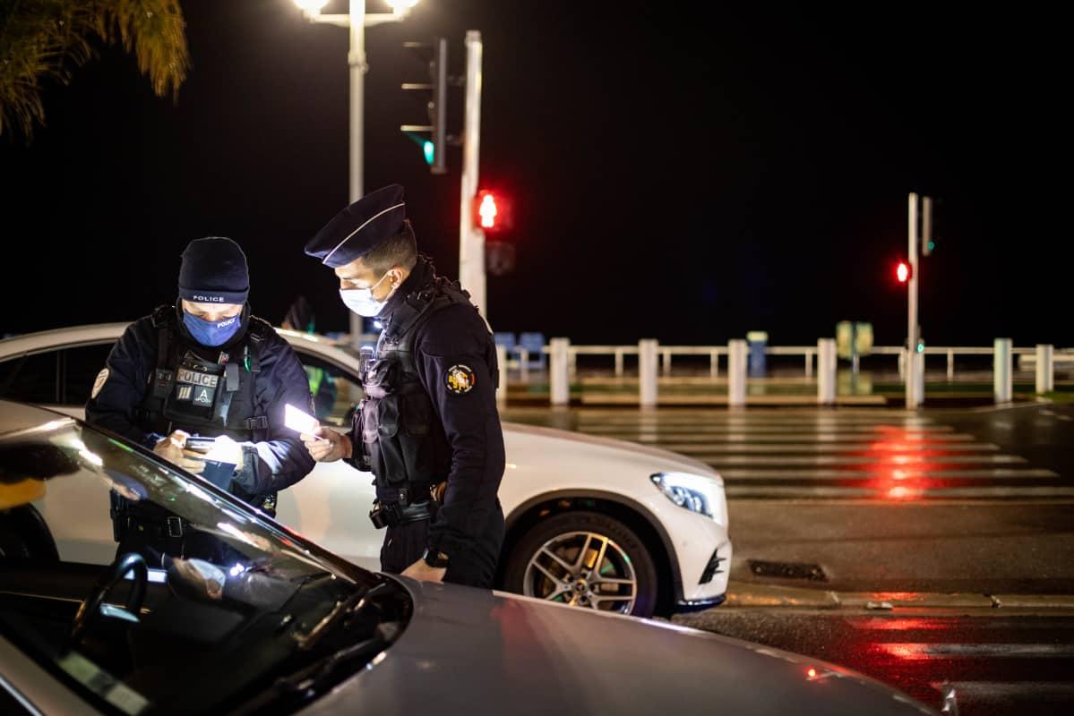 Poliisit tarkistavat autoilijan papereita pimeällä.