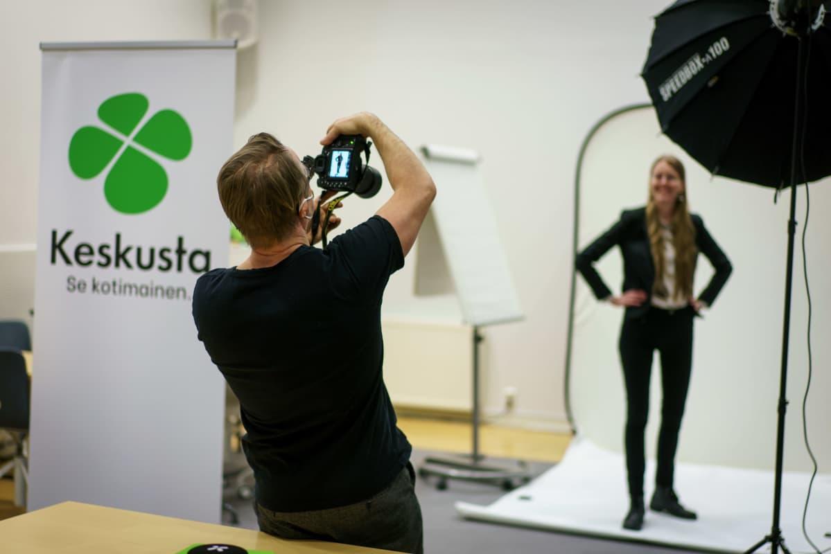 Valokuvaaja kuvaa tilapäisessä studiossa Keskustapuoleen kuntavaaliehdokasta. Vasemmalla keskustapuolueen banderolli.