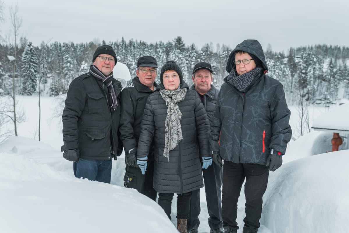 Sisarukset seisovat lumisessa maisemassa