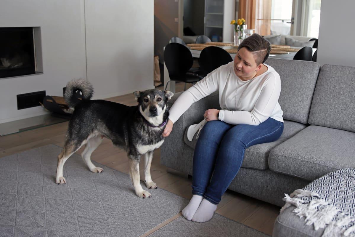 Juvalainen Anna-Mari Hangas-Tuovinen silittää koiraa etätyöpäivänsä ohessa.