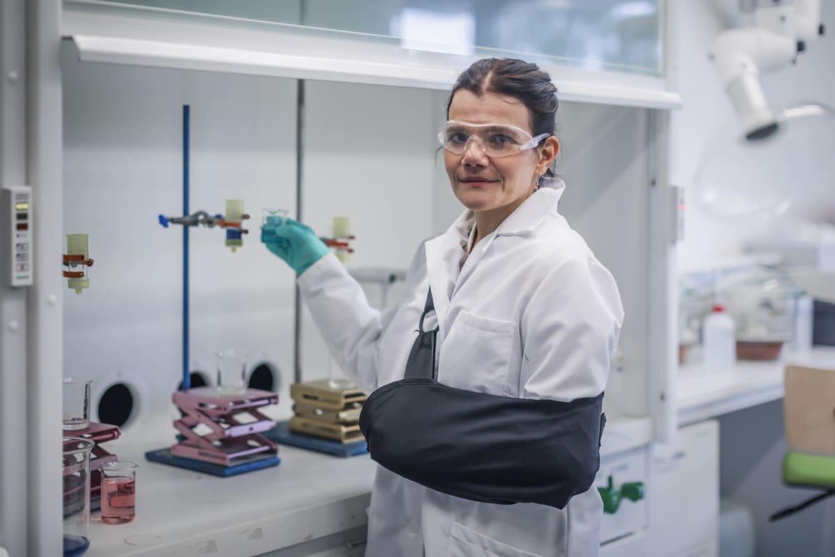 Nainen valkoisessa takissa tutkimuslaboratoriossa.