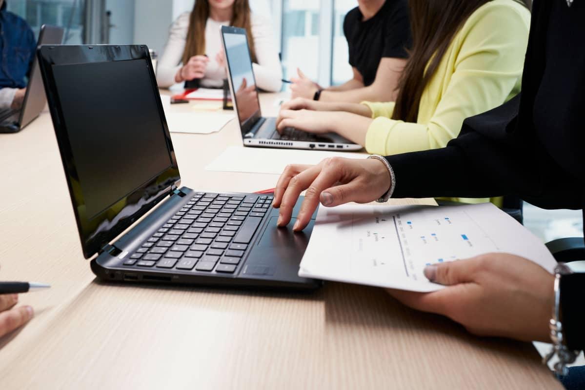 I förgrunden syns en person som studerar på datorn och har anteckningar framför sig. I bakgrunden syns fler personer som antecknar på dator eller på papper.