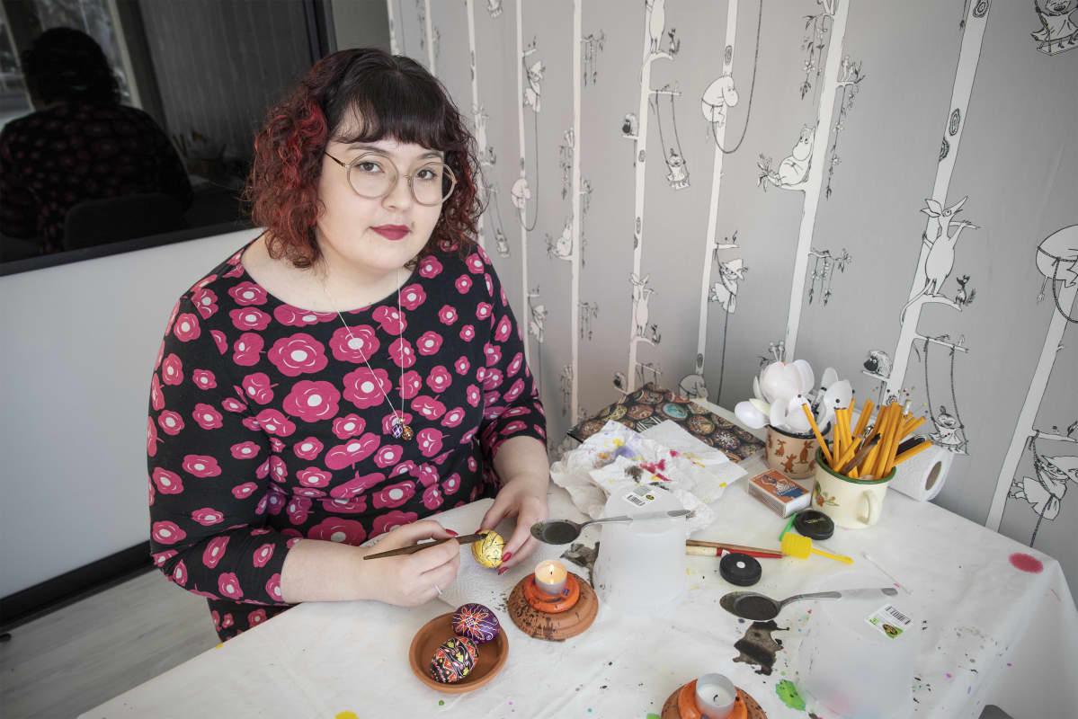 Hanna Lintu maalaa keltaista pääsiäismunaa kotonaan pöydän ääressä.