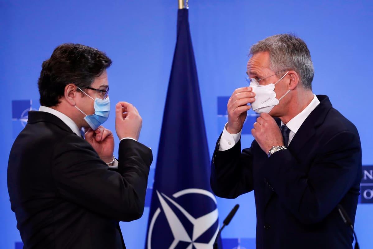 Ukrainan ulkoministeri ja Naton pääsihteeri asettavat maskeja kasvoilleen. Miehillä on tummat puvut ja kravatit. Taustalla on Naton lippu.