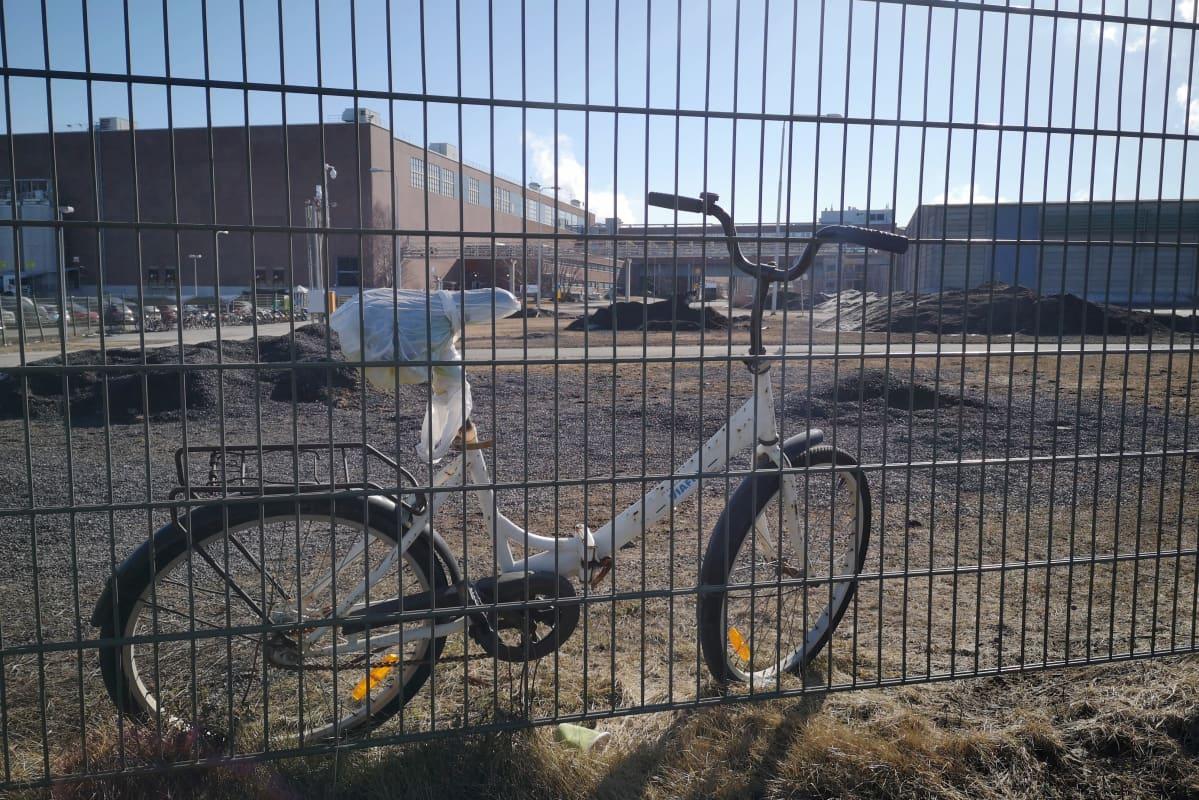 Polkupyörä nojaa Stora Enson Veitsiluodon paperitehtaan aitaa vasten, taustalla näkyy punatiilisiä tehdasrakennuksia.