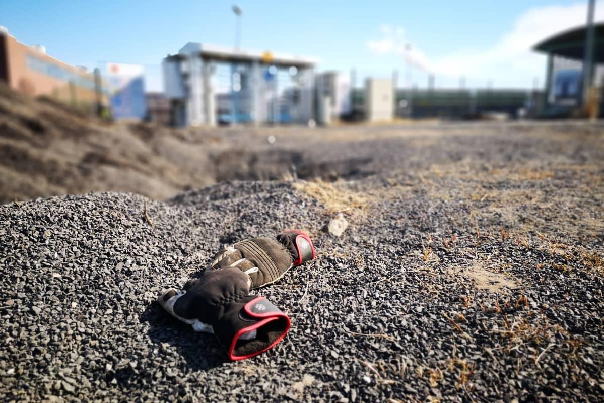 Työhanskat soralla. Taustalla näkyy Stora enson Veitsiluodon tehtaan portti.