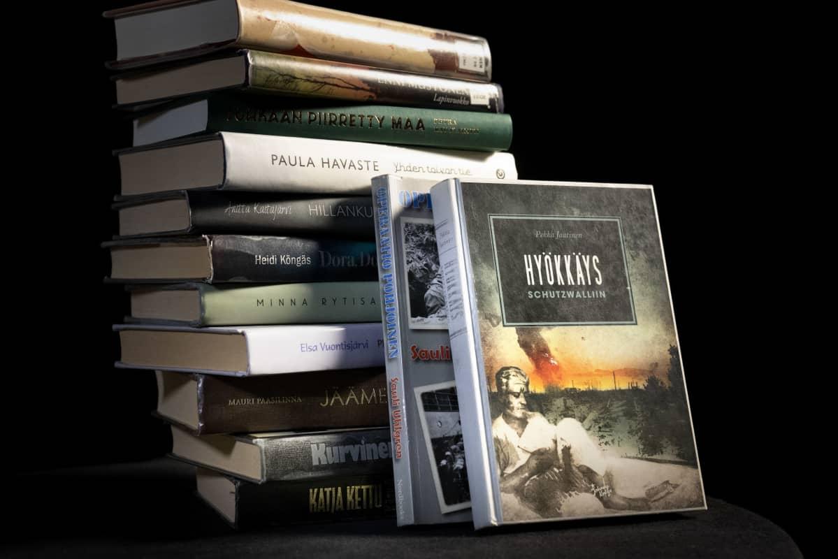 Lapinsotaa käsitteleviä kirjoja pinossa.