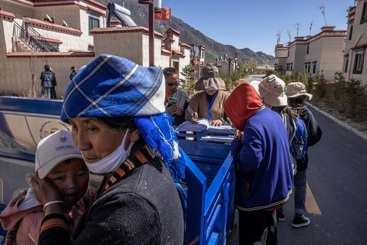 Joukko ihmisiä. Etualalla nainen lapsi sylissään. Taustalla väestönlaskijoita.