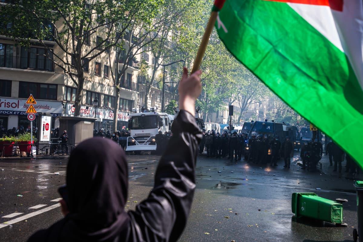 Nainen lippu kädessään. Kauempana mellakkapoliisien rivi.
