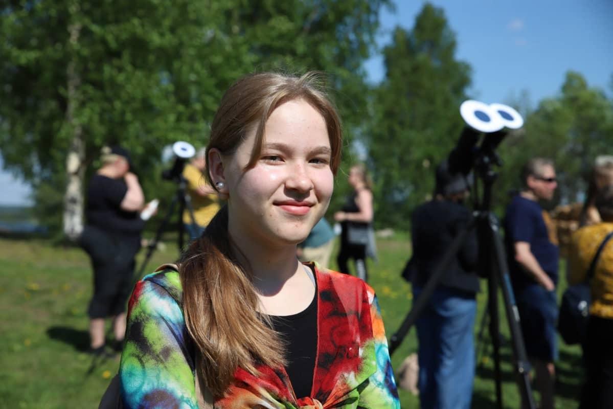 Nuori nainen katsoo auringonpimennystä rovaniemellä aurinkoisessa säässä