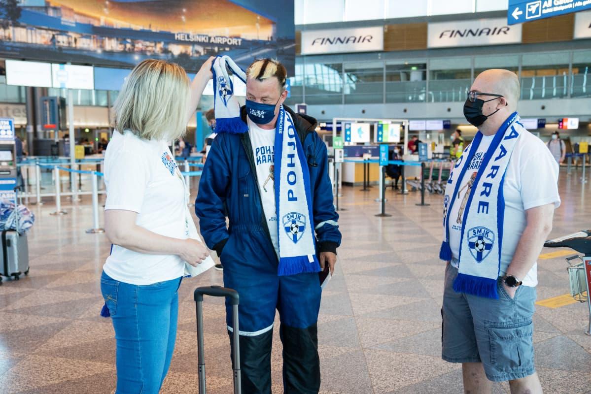 Kanssamatkustaja ihailee Suomen Maajoukkueen Kannattajat ry:n toiminnanjohtaja Kimmo-Jussi Hartikaisen asua