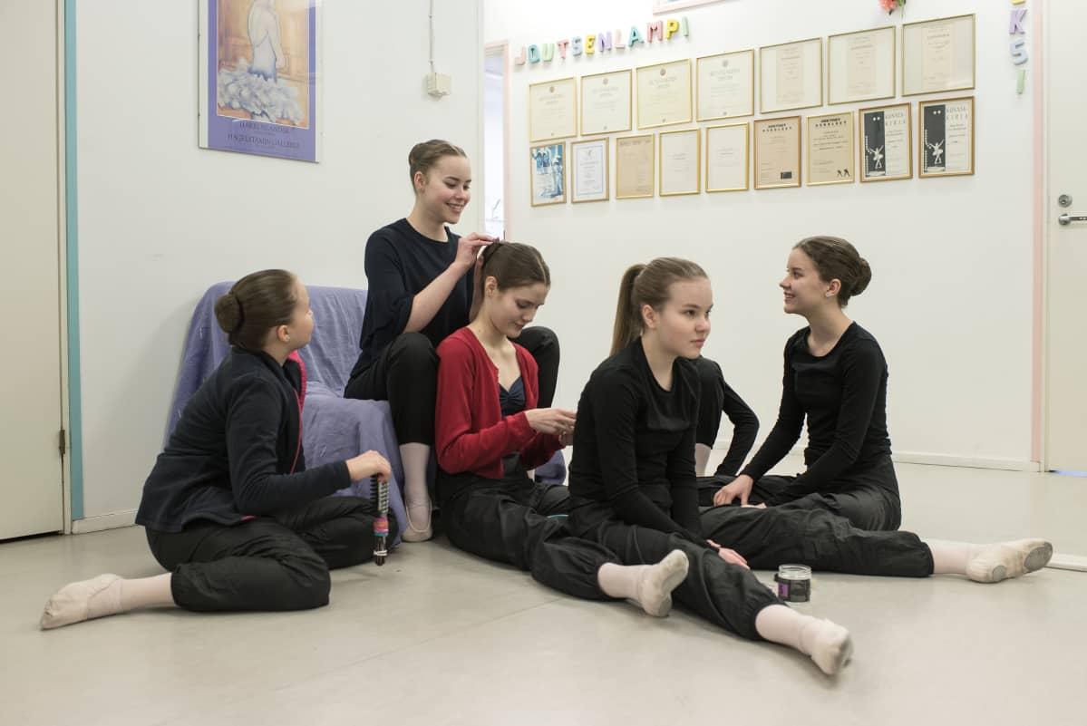 Balettitanssijat valmistautuvat harjoituksiin ja tekevät toisilleen nutturoita.