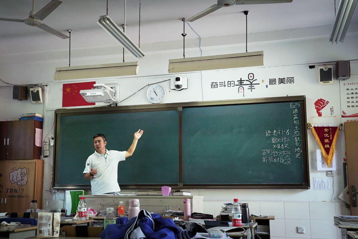 Opettaja seisoo vihreän liitutaulun edessä.