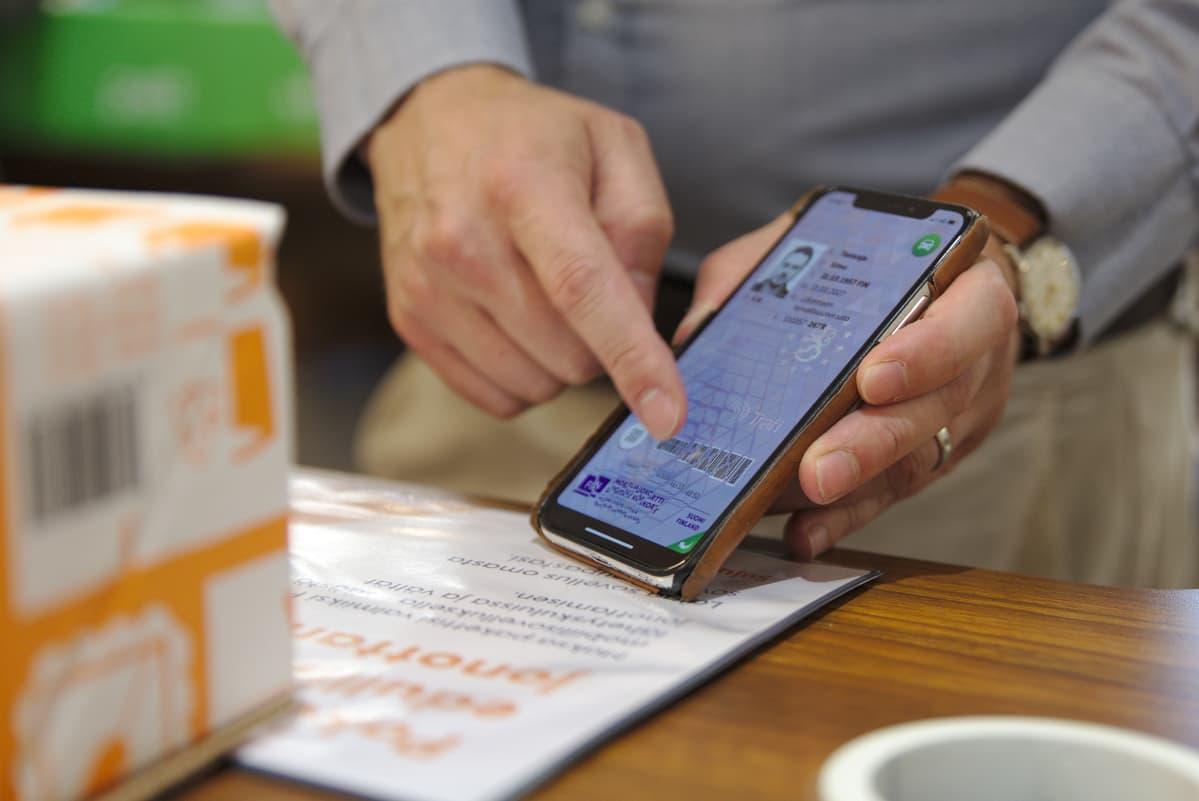 Posti mobiiliajokortti kädessä tiskillä