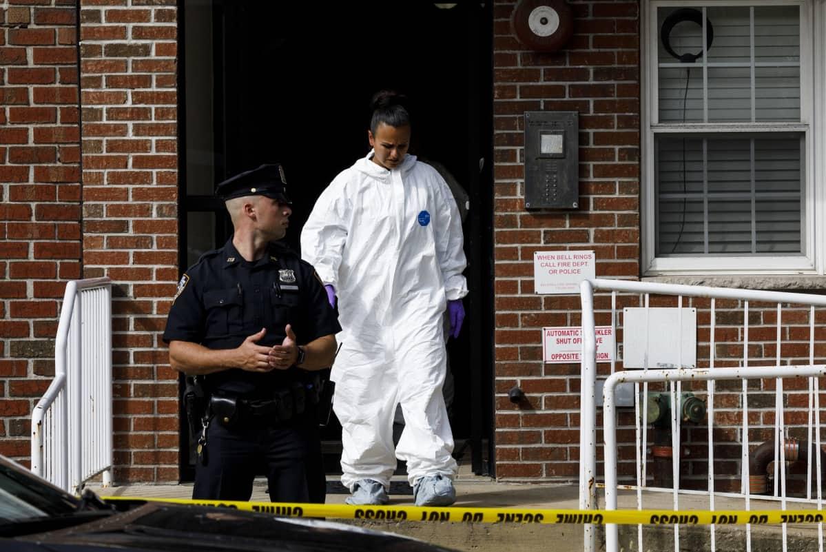 Poliisi vartioi taloa. Talosta tulee suojapukuinen rikospaikkatutkija.